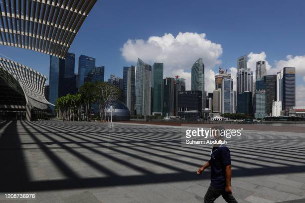 Man wearing protective mask walks at Marina Bay Sands with the Central Business District seen in the background on April 1, 2020 in Singapore. The...