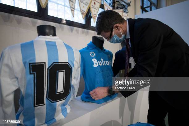 """Man wearing protective prepares Diego Armando Maradona football shirts for auction during the preparation of the """"Sport Memorabilia"""" auction on..."""