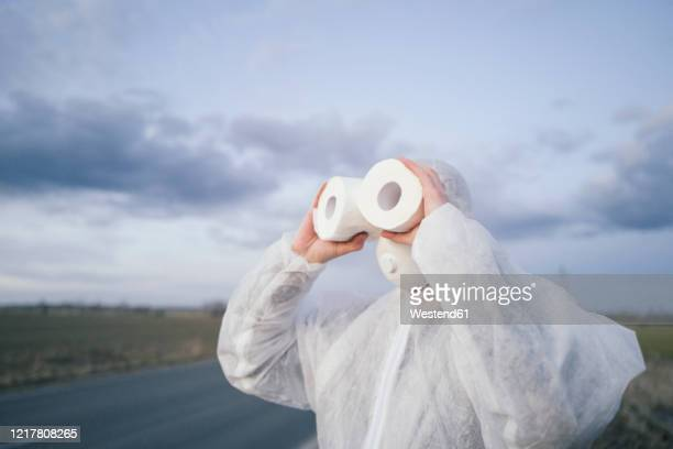 man wearing protective suit and mask using toilet rolls like binoculars - funny surgical masks stock pictures, royalty-free photos & images