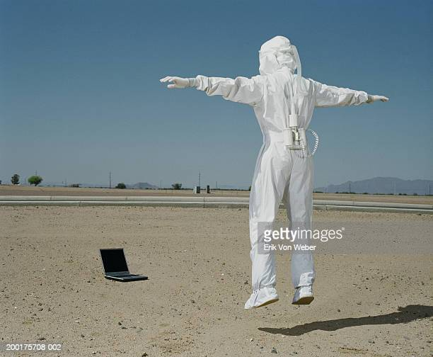 Man wearing protective suit jumping in front of laptop, rear view