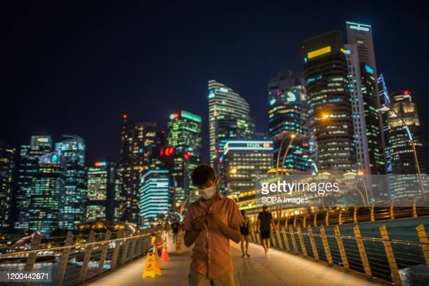 Man wearing protective surgical masks walks along the Merlion Park, a major tourist attraction in Singapore. Singapore declared the Coronavirus...