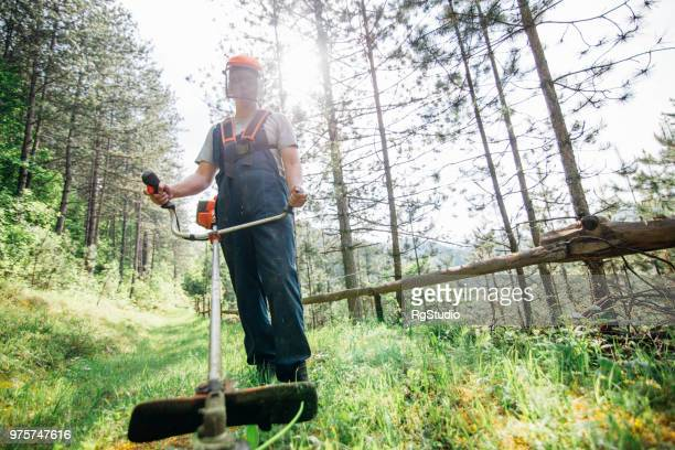 man wearing protective workwear mowing the lawn - scythe stock photos and pictures