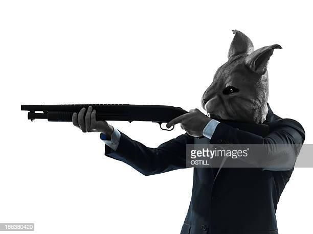 one caucasian man rabbit mask hunting with shotgun portrait in silhouette studio on white background