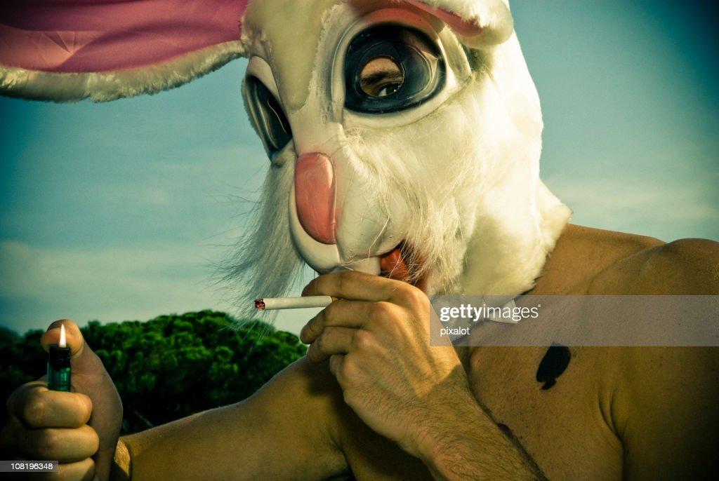 Man Wearing Rabbit Mask Lighting Cigarette : Stock Photo