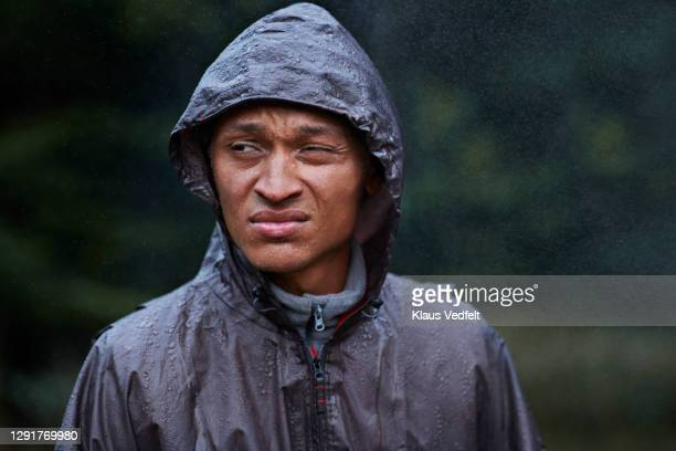 man wearing raincoat - grimacing stock pictures, royalty-free photos & images