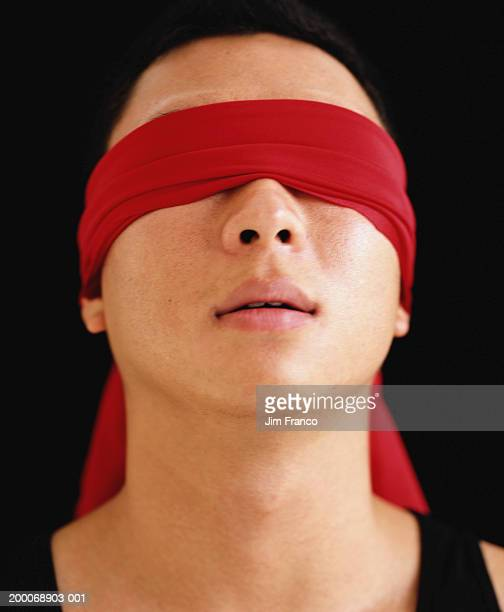 Man wearing red blindfold, close-up