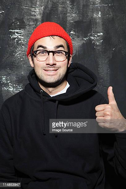 Man wearing red knit hat with thumbs up at party