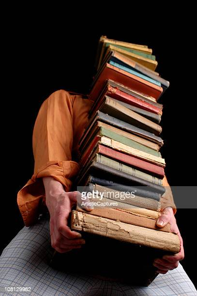 man wearing retro clothing carrying large stack of old books - oudheden stockfoto's en -beelden