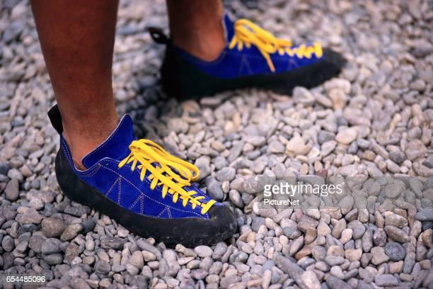 Man Wearing Rock Climbing Shoes on Gravel