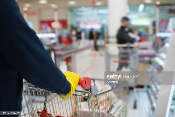 man wearing rubber gloves and holding shopping cart in a line with social distancing - panic buying stock pictures, royalty-free photos & images