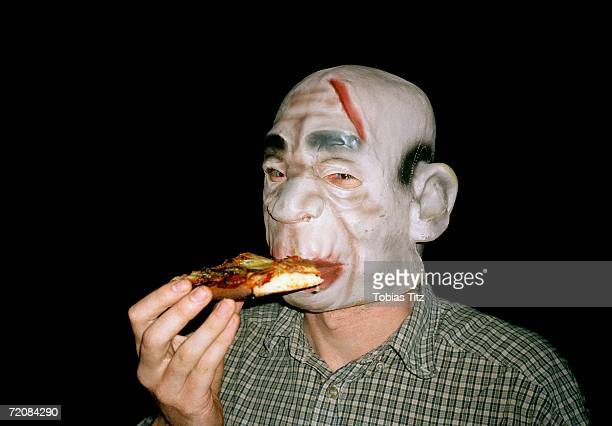 man wearing rubber monster mask and eating pizza - halloween party stock photos and pictures