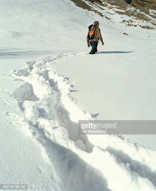man wearing rucksack walking through deep snow, rear view - deep snow stock pictures, royalty-free photos & images
