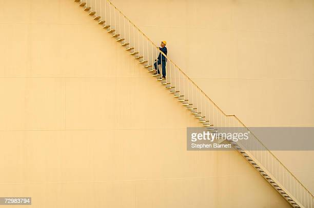 man wearing safety clothing ascending stairs of oil tank - silo stock photos and pictures
