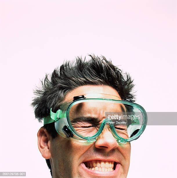 Man wearing safety goggles, grimacing, close-up