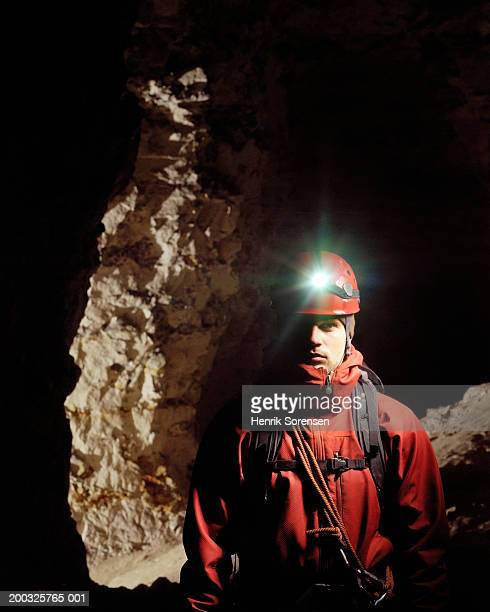 man wearing safety helment and torch in cave, portrait - spelunking stock pictures, royalty-free photos & images