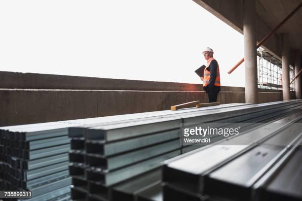 man wearing safety vest in building under construction - baumaschine stock-fotos und bilder