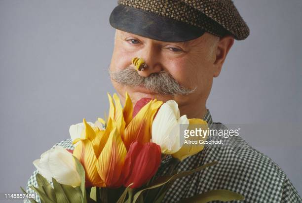 A man wearing sailor hat holding tulips with a fake bee on his nose US 1984