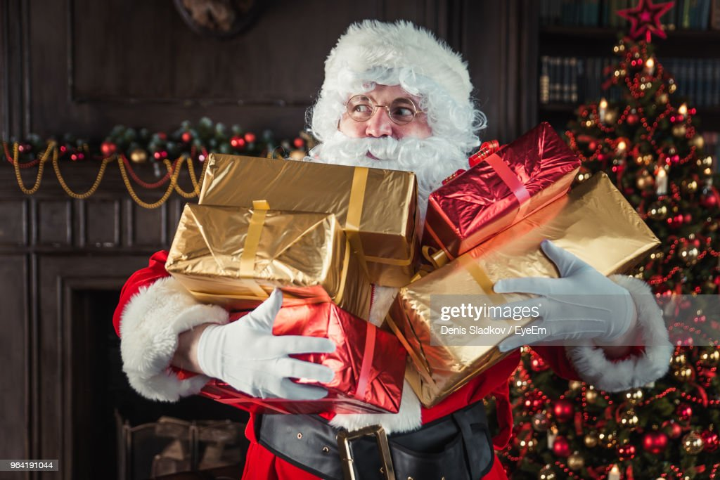 Man Wearing Santa Claus Costume Holding Christmas Presents At Home : Stock Photo