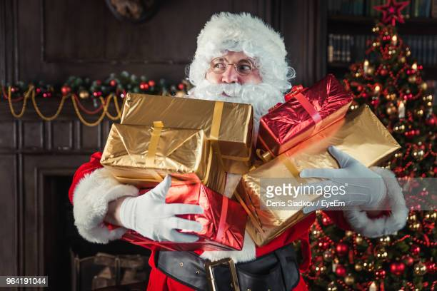 man wearing santa claus costume holding christmas presents at home - santa stock photos and pictures