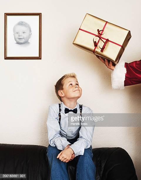 Man wearing santa costume handing boy (8-10) gift-wrapped present