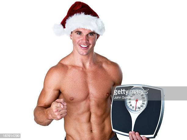 Man wearing Santa hat and holding a scale