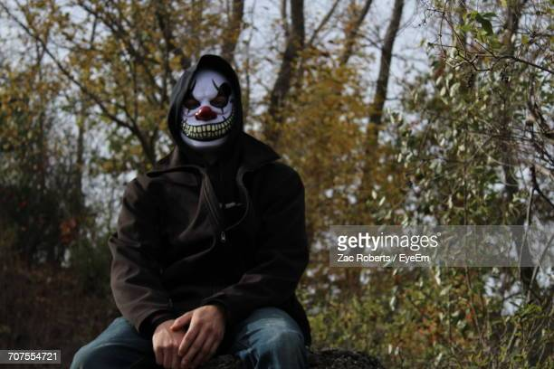 man wearing scary clown mask against trees - scary clown stock photos and pictures