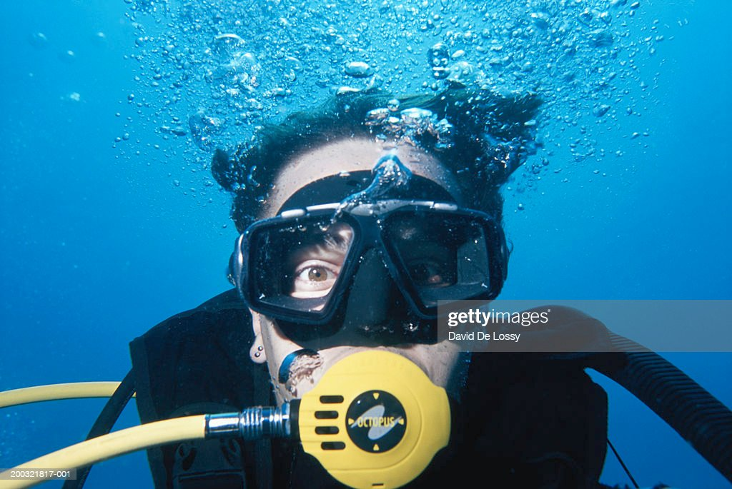 Man wearing scuba mask, underwater view, close-up : Stock Photo