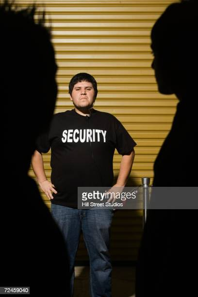 man wearing security shirt with hands on hips - doorman stock photos and pictures