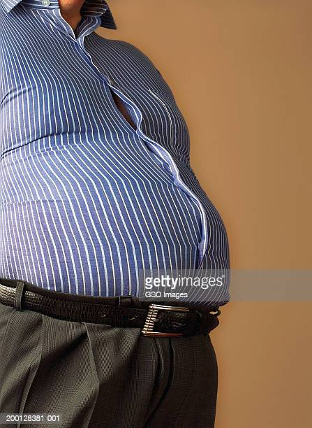 Man wearing shirt straining against pot belly, mid section