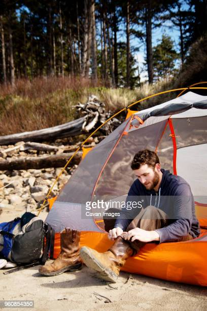 Man wearing shoes while sitting in tent