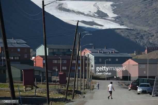 A man wearing shorts and a tshirt walks in the town center as the melting Longyear glacier looms behind during a summer heat wave on Svalbard...