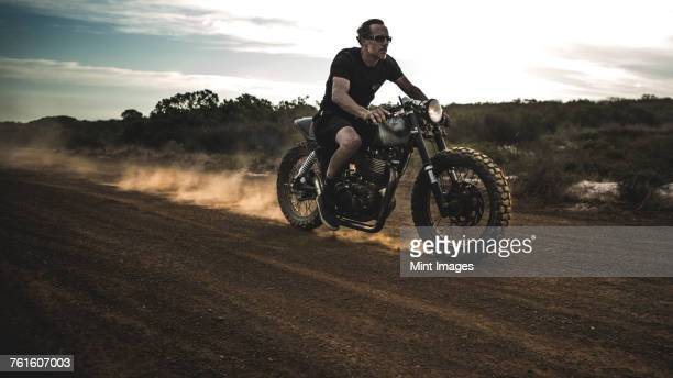 Man wearing shorts and sunglasses riding cafe racer motorcycle on a dusty dirt road.