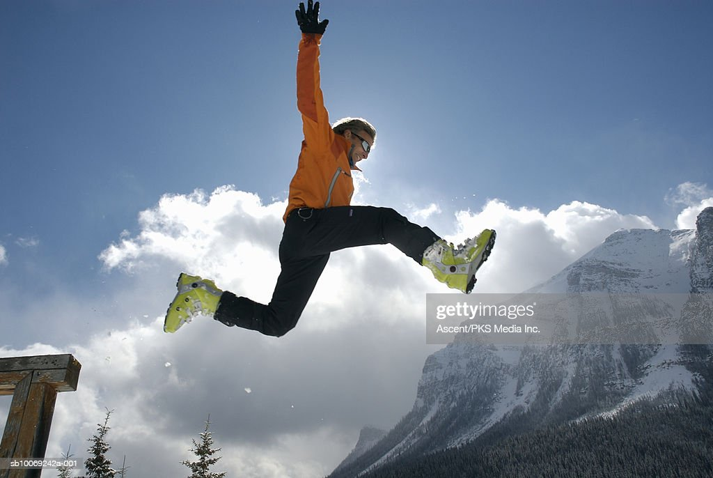 Man wearing ski boots jumping in mid air, low angle view, mountains in background : Stockfoto