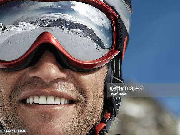 man wearing ski goggles, smiling, close-up - ski goggles stock pictures, royalty-free photos & images
