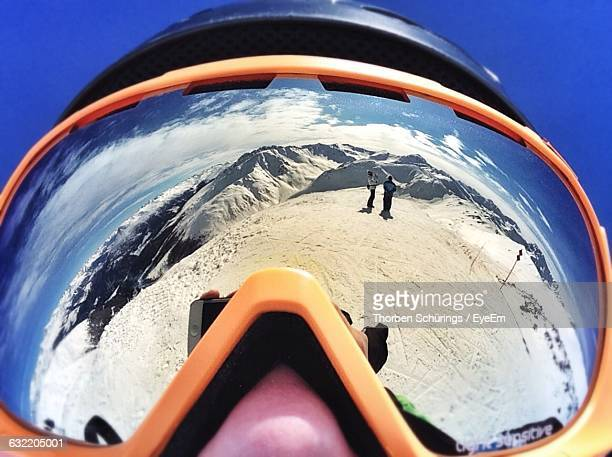 Man Wearing Ski Goggles With Reflection Of People On Snow Covered Field