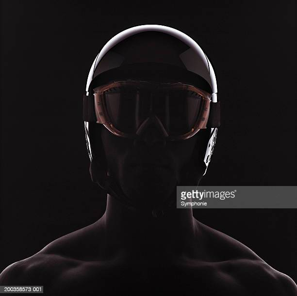Man wearing ski helmet and goggles, close-up, backlit