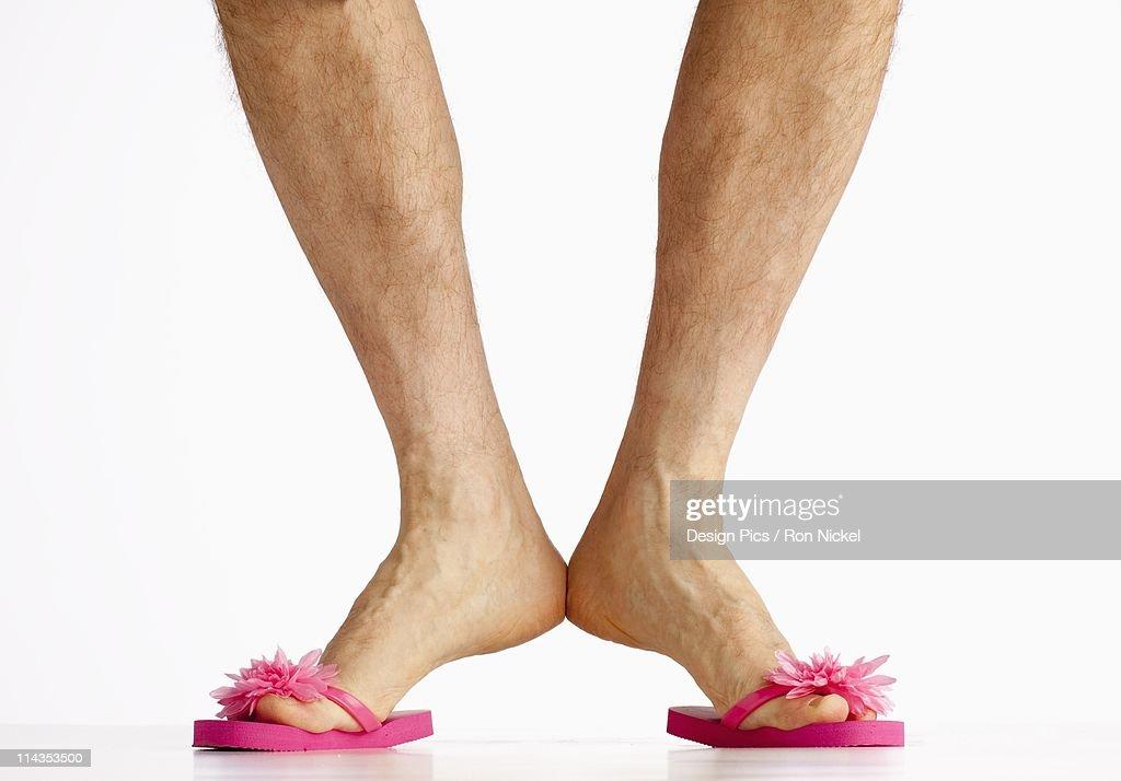 A Man Wearing Small Pink Flip Flops : Stock Photo