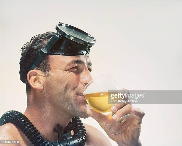 Man wearing snorkel drinking beer, close-up