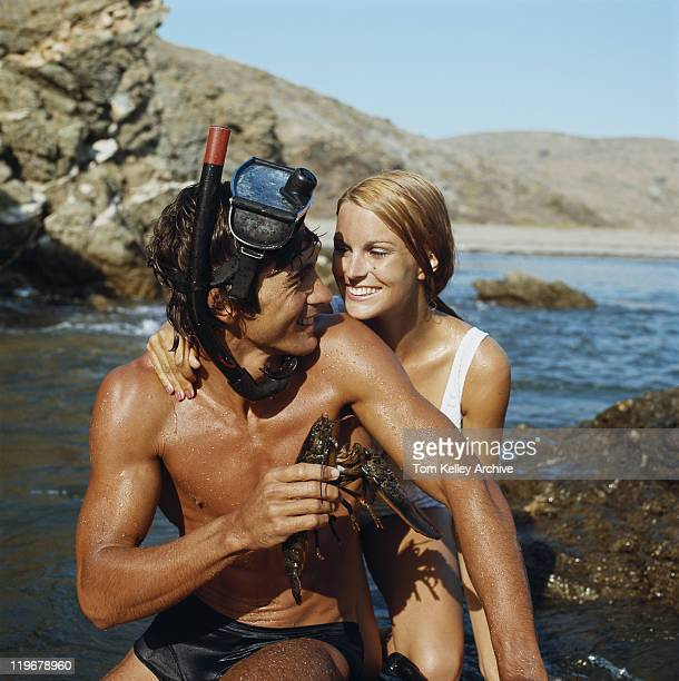 Man wearing snorkel, holding lobster beside woman, smiling