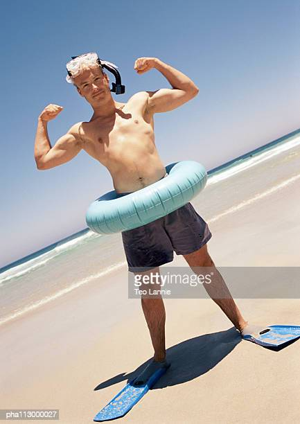 Man wearing snorkeling gear and inner tube, flexing at the beach.