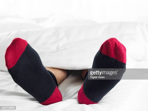 Man Wearing Socks Underneath a Duvet in Bed
