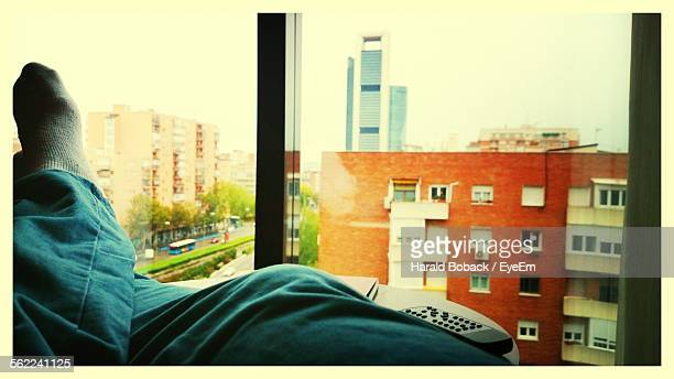 Man Wearing Socks With Legs Crossed At Ankle On Table Against Glass Window Of Abba Castilla Plaza Hotel Room
