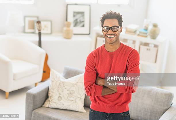 Man wearing spectacles standing in living room