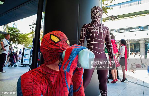 A man wearing spiderman costume drinks water while another spiderman waits during a cosplay event as the temperature in Nagoya climbed up to 349...
