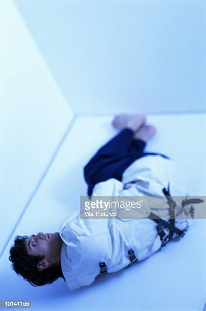 man wearing strait jacket, lying on floor, elevated view (blue tone) - straight jacket stock pictures, royalty-free photos & images