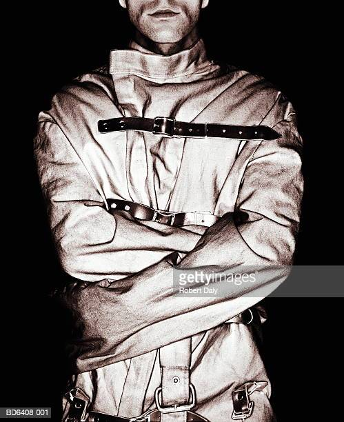 man wearing straitjacket, mid section (toned b&w) - straight jacket stock pictures, royalty-free photos & images