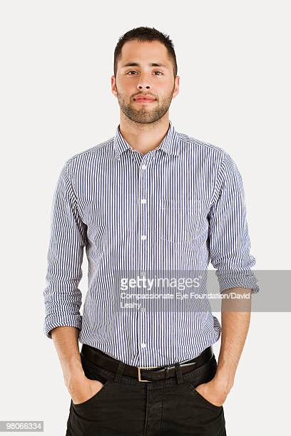 Man wearing striped shirt with hands in pockets