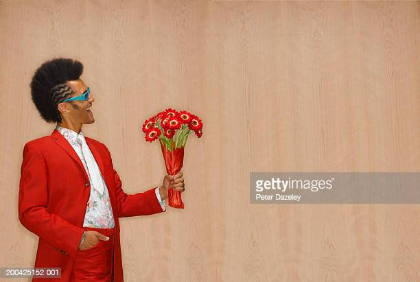 Man wearing suit and sunglasses, holding bunch of gerberas, side view