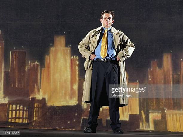 Man wearing suit and trenchcoat, painted skyline in background