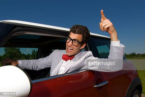Man Wearing Suit Driving in Little Red Car
